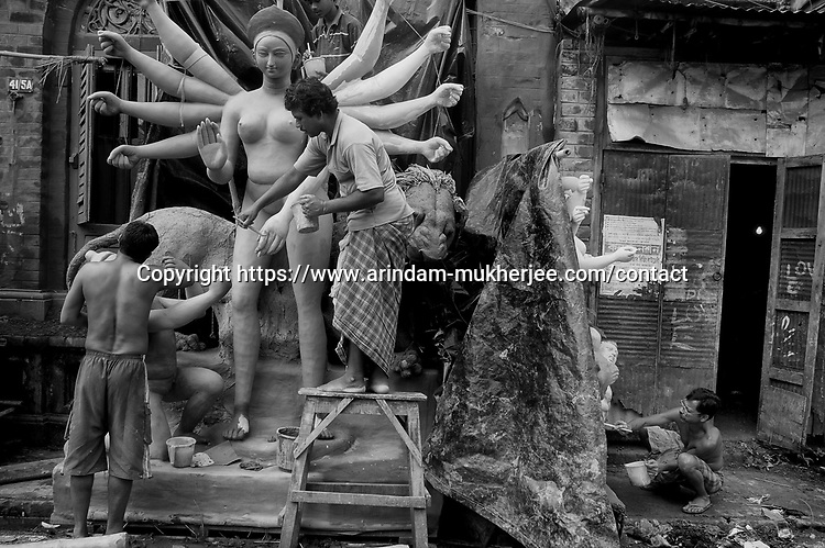 INDIA (West Bengal - Calcutta)  2008, Artisans working at Kumortuli. Kumortuli in North Calcutta is the hub of  idol makers. During the other time of the year the artists engage themselves in prepairing other idols and masks depending on the assignments. But the most of the earning they aquire from making Durga idols. A Durga idol can cost up to 7000 usd. Which is a big price in Indian Currency.  Durga Puja Festival is the biggest festival among bengalies.  As Calcutta is the capital of West Bengal and cultural hub of  the bengali community Durga puja is held with the maximum pomp and vigour. Ritualistic worship, food, drink, new clothes, visiting friends and relatives places and merryment is a part of it. In this festival the hindus worship a ten handed godess riding on a lion armed wth all possible deadly ancient weapons along with her 4 children (Ganesha - God for sucess, Saraswati - Goddess for arts and education, Laxmi - Goddess of wealth and prosperity, Kartikeya - The god of manly hood and beauty). Durga is symbolised as the women power in Indian Mythology.  In Calcutta people from all the religions enjoy these four days of festival in the moth of October. Now the religious festival has become the biggest cultural extravagenza of Calcutta the cultural capital of India. Artistry and craftsmanship can be seen in different sizes and shapes in form of the idol, the interior decor and as well as the pandals erected on the streets, roads and  parks.- Arindam Mukherjee