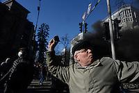 An elder rioter hurls paving stones beyond the barricades. Kiev, Ukraine