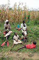 Kenya. Rift Valley Province. Matisi. Mothers and children, all workers for the harvesting season of maize, take a rest and seat on the ground in the grass.  © 2004 Didier Ruef
