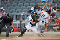 Fayetteville Woodpeckers catcher Michael Papierski (28) can't hold on to the ball as he tags Ryan Aguilar (11) of the Carolina Mudcats as home plate umpire Jake Bruner looks on at SEGRA Stadium on May 18, 2019 in Fayetteville, North Carolina. The Mudcats defeated the Woodpeckers 6-4. (Brian Westerholt/Four Seam Images)