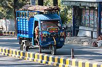 India, Dehradun.  Transporting Steel Pipes on a Three-wheeled Vehicle.