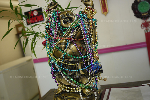 Bayou La Battre, Alabama.August 2010..Vietnamese restaurant with statue of Buddha covered in Mardi Gras beads -- a mix of traditions.