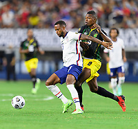DALLAS, TX - JULY 25: Kellyn Acosta #23 of the United States attempts to keep Cory Burke #9 of Jamaica away from the ball during a game between Jamaica and USMNT at AT&T Stadium on July 25, 2021 in Dallas, Texas.