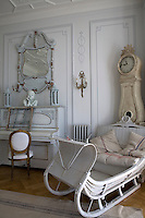 The wood panelled living room is furnished with an antique Swedish sleigh couch, a piano and a Mora clock