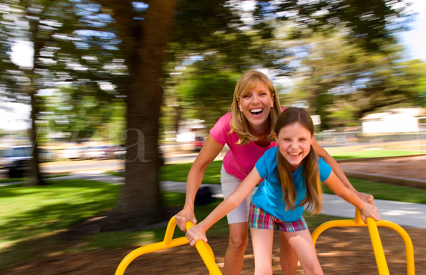 Mother and daughter having fun spinning on ride in playground