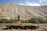 12 June 2013, Urrow Village, Bazarak District, Panjshir Province,  Afghanistan.  A man stands on the rusting remnants of Russian tanks that were left from the war with the Soviets on the banks of the Panjshir  river. Picture by Graham Crouch/World Bank