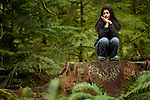 A young woman meditates on the stump of a massive old growth Douglas fir tree in Cathedral Grove, in MacMillan Provincial Park on Vancouver Island, British Columbia, Canada.