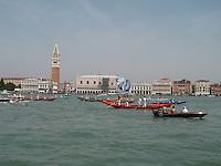 A traditional regatta of gondolas passes Venice's famous landmarks.
