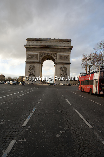 The worn pavement and cobble stone are seen in the foreground as a bus mooves toward the Place Charles De Gaulle and the Arch De Triumph in Paris france.