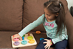 4 year old girl playing with color sorting peg and circles toy