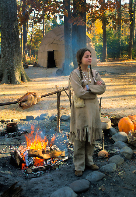Teenage historic interpreter demonstrates the lifestyle of a young Powhatan girl, such as Pocahontas, dressed in a deerskin dress and leggings tends a fire that roasts a turkey on a spit at the  Powhatan Indian Village on the Jamestown Settlement near Williamsburg; Virginia during the Foods and Feasts Festival