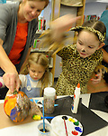 Natalie and Brinley Aglietti, 3, and Magdalena Osborn, 7, create some Halloween art at the Carson City Library Monday, Oct. 27, 2014. As part of the library's Halloween festivities, dozens of children decorated pumpkins or gourds and took part in a costume contest.