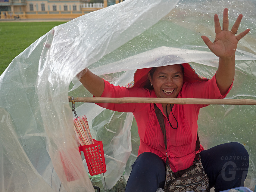 Phnom Penh street scenes and people during the Monsoon season and heavy rains. Cambodia A vendor covering herself with plastic sheets to take cover from the heavy rain.