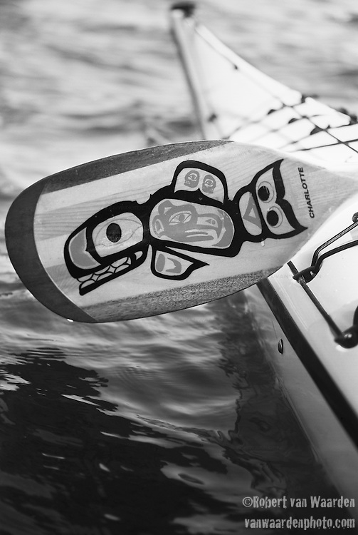 A wooden kayak paddle decorated in the style of the West Coast natives.