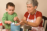3 year old boy cooking baking activity with grandmother Caucasian horizontal scooping and measuring ingredients