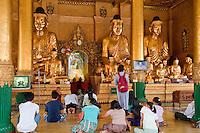 Myanmar, Burma.  Shwedagon Pagoda, Yangon, Rangoon.  Worshipers Praying at one of the many Buddha Shrines around the Stupa.