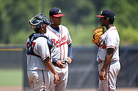 GCL Braves pitching coach Willie Martinez (43) talks with pitcher Oriel L Caicedo (11) and catcher Carlos Martinez (57) during the first game of a doubleheader against the GCL Yankees 1 on July 1, 2014 at the Yankees Minor League Complex in Tampa, Florida.  GCL Yankees 1 defeated the GCL Braves 7-1.  (Mike Janes/Four Seam Images)