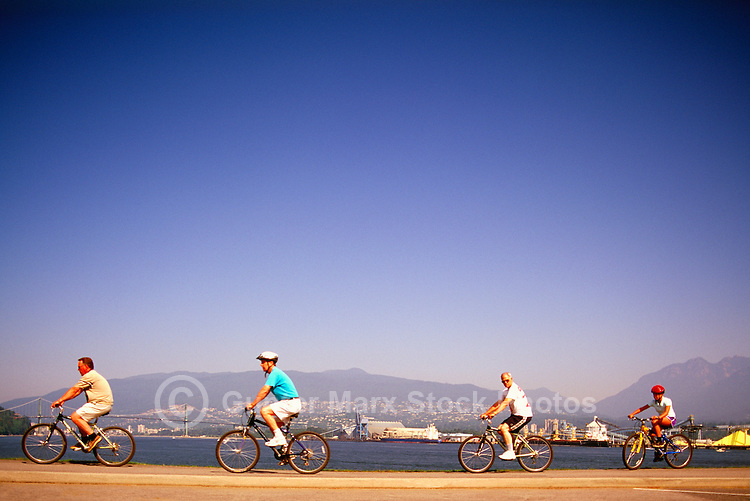 Stanley Park, Vancouver, BC, British Columbia, Canada - Men cycling on Seawall along Burrard Inlet in Summer - Lions Gate Bridge, West Vancouver, and North Shore Mountains in background