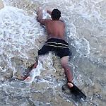 A young man plays in the shallows of Waikiki Beach, Hawaii.