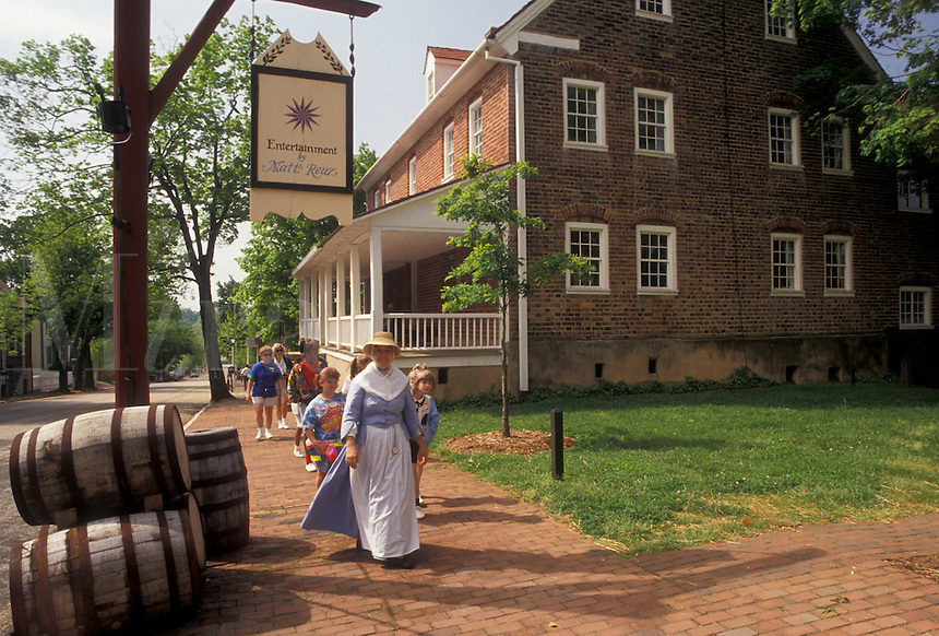 AJ3401, Old Salem, Moravian, Winston-Salem, North Carolina, A group of people walk with an interpreter along the streets of Old Salem, a living history restoration of the Moravian church town of Salem founded in 1766, in Winston-Salem in the state of North Carolina.