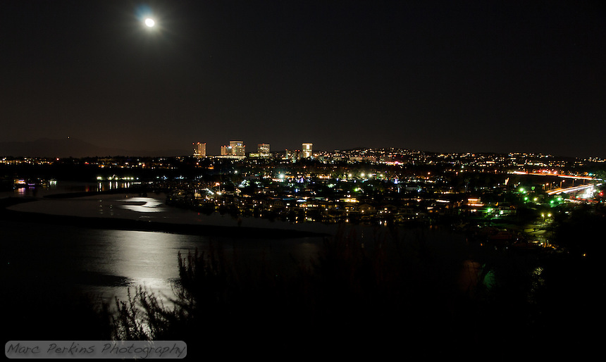 A moonlit view of Lower Newport Bay (and partially Upper Newport Bay) with PCH (Pacific Coast Highway) to the right and Newport Center's many tall buildings that surround Fashion Island in Newport Beach, CA.  Saddleback Mountain (Santiago Peak and Modjeska Peak) can be seen off in the distance, to the left.  This image is a minimally manipulated single-frame, long-exposure capture.