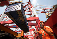 A dock worker directs the loading of a container onto a truck at the new Qianwan container terminal of the Qingdao Port in Qingdao, China.<br /> 13 August, 2007.