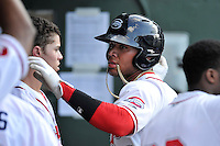 Second baseman Yoan Moncada (24) of the Greenville Drive is congratulated after scoring a run in the first inning of a game against the Augusta GreenJackets on Thursday, July 16, 2015, at Fluor Field at the West End in Greenville, South Carolina. The Cuban-born 19-year-old Red Sox signee has been ranked the No. 1 international prospect in baseball by Baseball America. Greenville won, 11-5. (Tom Priddy/Four Seam Images)