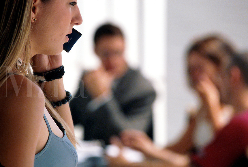A young woman talks on a cell phone at a buisiness meeting.