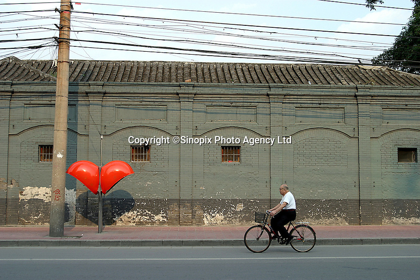 A man heads home in the evening on his bicycle in Beijing, China..17 Aug 2004