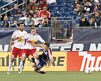 New England Revolution midfielder Kelyn Rowe (11) hits the ground after battle for ball with New York Red Bulls defender Jan Gunnar Solli (8) and New York Red Bulls defender Wilman Conde (2). Despite a red-card man advantage, in a Major League Soccer (MLS) match, the New England Revolution tied New York Red Bulls, 1-1, at Gillette Stadium on September 22, 2012.