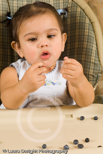 10 month old baby girl in high chair feeding self fuit berries blueberries Hispanic vertical