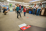 Alex Wells watches his ball fly during the Mini Golf Night at the Carson City Library on Friday May 9, 2014. Kids and parents built a custom mini golf course throughout the library using anything at their disposal and engineering ideas to make a difficult course. Everything from tables to shelves were used to create creative courses.<br /> (Photo by Kevin Clifford/Nevada Photo Source)