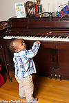 17 month old toddler boy trying out piano keys