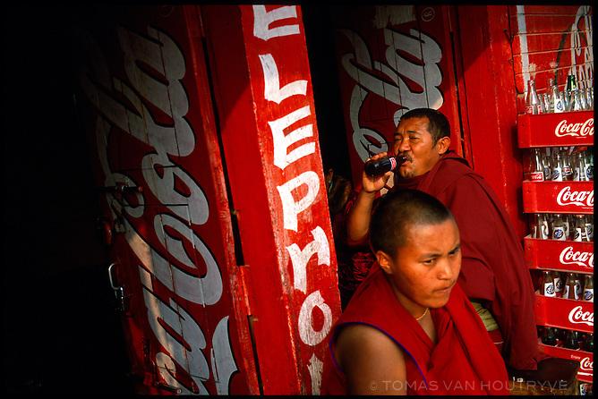 Buddhist monks drink Coca Cola at a shop near the Boudha Stupa, a sacred Tibetan Buddhist site in Kathmandu on 18 Febduray 2004.