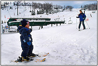 A young child/toddler has his first lesson in snow skiing. Photo taken in Pennsylvania, but can be used to illustrate children learning how to ski anywhere. Model released image. Mother, who is also learning how to ski in this photo, is skiing into scene from right.