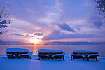 Three snow covered benches look out over Lake Coeur D' Alene in the soft evening light of a winter day. Idaho.