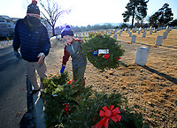 Greg McDaniel of Springdale and his son, Knox McDaniel, 8, work together Saturday, Jan. 9, 2021, while collecting the holiday wreaths at the Fayetteville National Cemetery. The wreaths were placed in front of each grave in the cemetery in December by volunteers through the Wreaths Across America program and were collected by groups of volunteers organized by the Fayetteville National Cemetery Advisory Council who worked in shifts because of the pandemic. Efforts in the past to recycle the metal in the wreaths did not attract enough volunteers to continue to make the effort feasible, so the wreaths had to be discarded. Visit nwaonline.com/210110Daily/ for today's photo gallery. <br /> (NWA Democrat-Gazette/Andy Shupe)