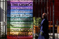 """NEW YORK, NEW YORK - MARCH 15: A man walks in front a placard posted on a church fence on March 15, 2021 in New York. With a """"Responsum ad dubium"""" the Catholic Church says that it does not bless same-Sex marriage.  (Photo by Emaz/VIEWpress)"""