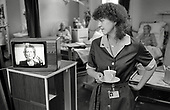 1986: a domestic worker at St.Charles Hospital, Notting Hill, newly contracted out to cleaning company Mediclean, watches a televised speech by Prime Minister Margaret Thatcher.