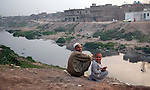 A local man sits with his son outside his home in Rawalpindi ten kilometres from Islamabad. The capital of Pakistan has been in turmoil  recently as the Government faces political upheaval and the ever present threat of the Taliban.