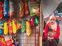 General life and environs in the Malate, Manila area and Manila Bay, Philippines. Sidewalk store along Manila Bay and a Muslim women looking on, Manila, Philippines