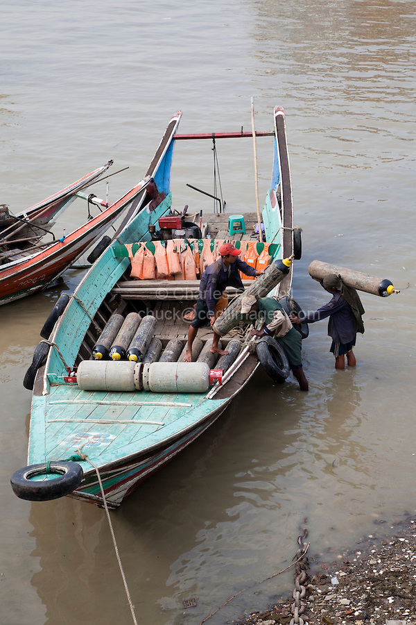 Myanmar, Burma, Yangon.  Manually Loading Oxygen Bottles into Small Boat, Yangon River.