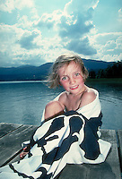 Towel-wrapped, smiling young girl at lake. Leoni. Germany.