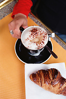 Woman in cafe holding a cup of cappuccino with croissant in foreground
