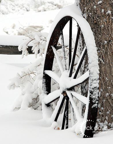 A rustic steel wagon wheel in the winter snow.