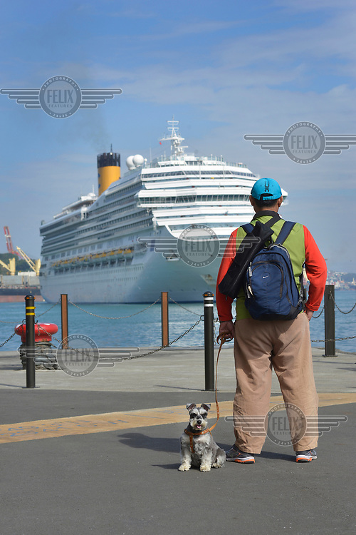 A man and his schnauzer watches a vast Star Cruises ocean liner manoevering out of the port.