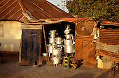 The Gambia. Shiny aluminium pots and pans on sale from a rusty make shift, derelict shed.