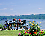 Germany, Bavaria, Upper Bavaria, Ammer Lake, Utting: couple sitting on bench, cyclists, resting
