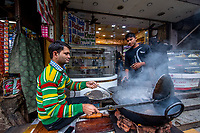 India, New Delhi, men cooking puri while on their phone.