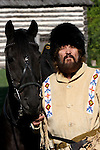 A Russian Cossack posing with his horse in front of a log cabin